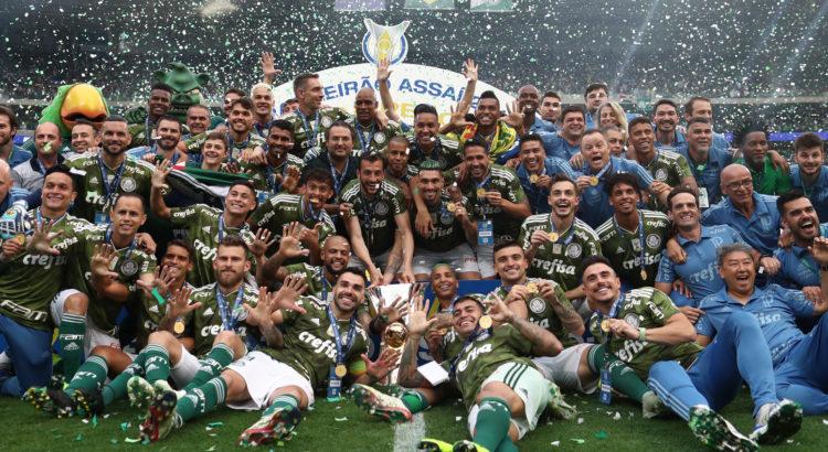 Jogadores do Palmeiras comemoram o título de campeão brasileiro de 2018 com as medalhas e o troféu.
